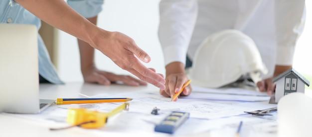 Designer und architekten arbeiten gemeinsam an entwürfen für neue bauprojekte.
