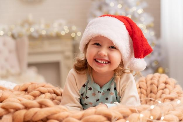 Designerdecken von merino beige! lachendes kind in nikolausmütze. hinter dem mädchen im hintergrund steht ein weihnachtsbaum am fenster