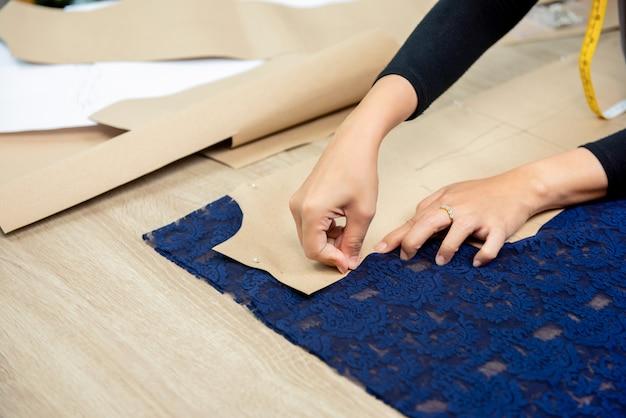 Designerhände, die papiermuster auf gewebe am tisch feststecken