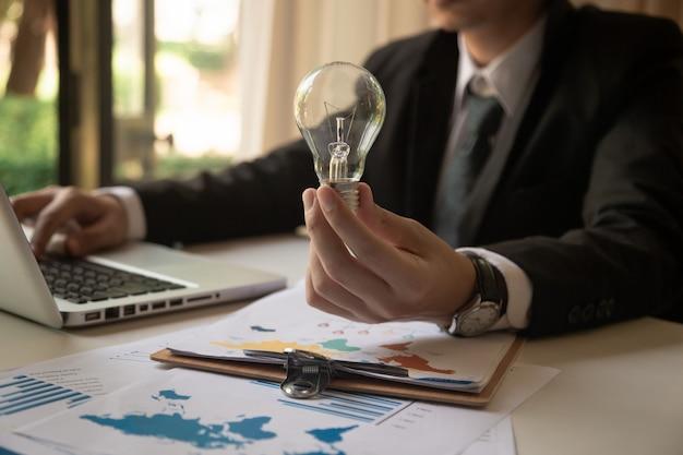 Designerhand, die kreative geschäftsstrategie mit glühlampe als konzept zeigt