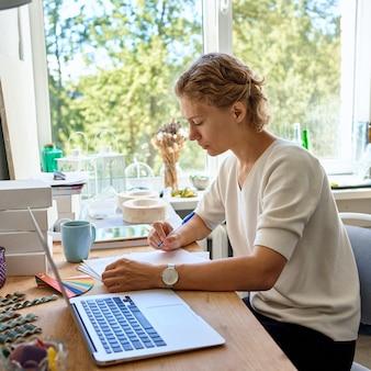 Designerin des jungen unternehmerinnenschreibens auf papierblatt, ernsthaftes denken und planen der frau