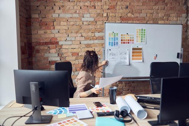 Designerin, die blaupausenpapier und farbmuster an bord anbringt, während sie an der neuen innenausstattung arbeitet