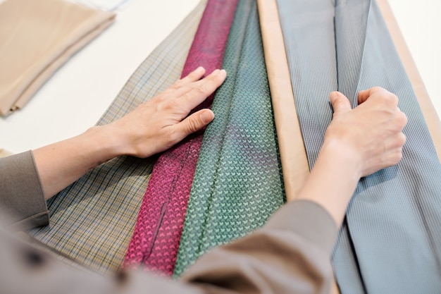 Designerin, die die geeignete farbe und textur des stoffes auswählt, während sie durch textilien nach einer neuen kollektion sucht