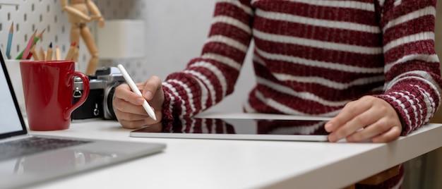 Designerin, die mit digitalem tablett auf weißem tisch mit modell-laptop, kamera, becher und zubehör arbeitet