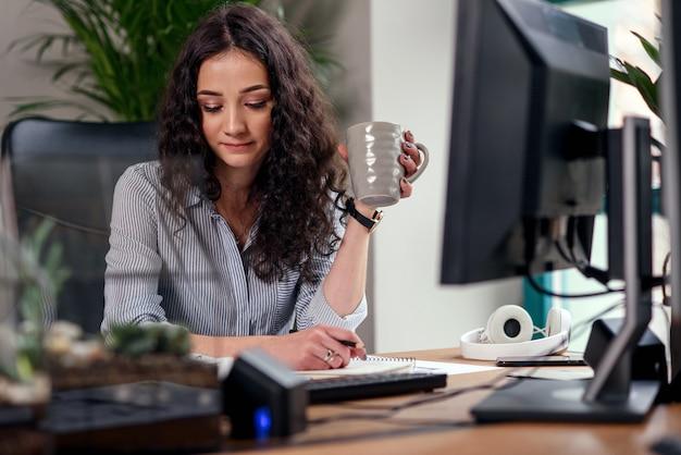 Designerin im büro, die mit farbmustern arbeitet. frau am arbeitsplatz macht ein foto der farbpalette auf smartphone.