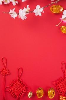 Designkonzept des chinesischen neuen mondjahres - schöner chinesischer knoten mit pflaumenblüte lokalisiert auf rotem hintergrund, flache lage, draufsicht, überkopflayout.