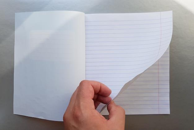 Designkonzept - draufsicht auf eine hochwertige männliche hand, die durch ein blatt blau gestreiftes notizbuch blättert. ansicht von oben, kopienraum, flache lage.