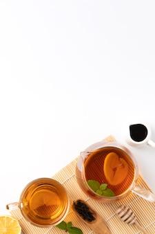 Designkonzept draufsicht auf honig schwarztee mit gelber zitrone und minze auf weißem tischhintergrund.