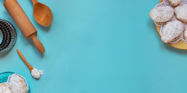 Designkonzept für die herstellung traditioneller zypern-kekse, backen von holzlöffeln, nudelholz, metallformen, zuckerpulver, draufsicht, flache lage, overhead, leerer kopierraum auf blauem hintergrund