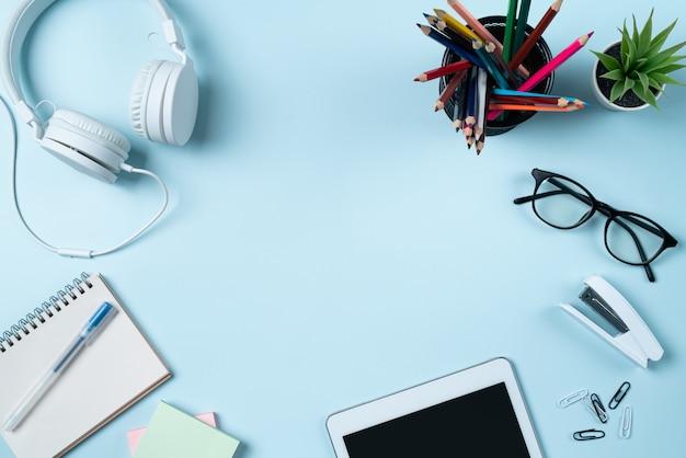 Designkonzept für online-lernen. blick von oben auf den studententisch mit tablet, kopfhörer und schreibwaren auf blauem tischhintergrund.