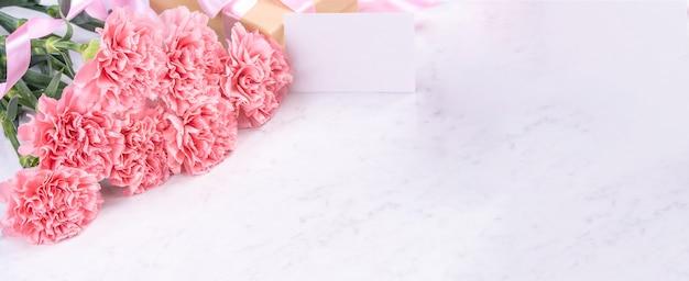Designkonzept - schöner haufen nelken auf weißem marmorhintergrund, draufsicht, kopienraum, nahaufnahme. muttertag geschenkidee inspiration.