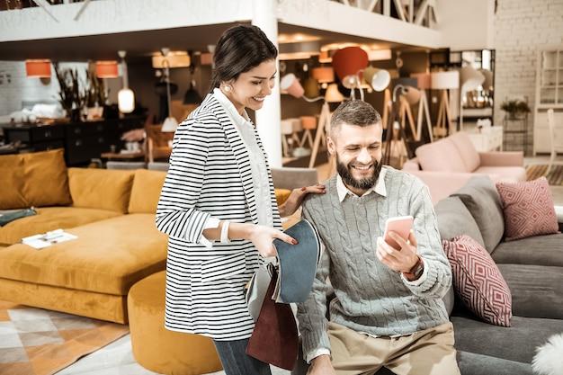 Designs auf dem smartphone. lachende gut aussehende familie, die auf smartphone-bildschirm schaut, während sie bündel stoffmuster trägt