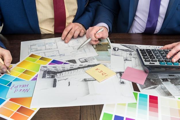 Designteam, das im büro unter hausprojekt arbeitet. wohnungsskizze mit farbpalette. modernes süßes zuhause.