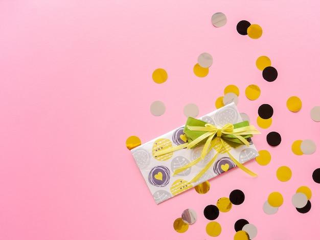 Designumschlag mit grünem band auf rosa. glückwunschkarte mit bunten konfetti.