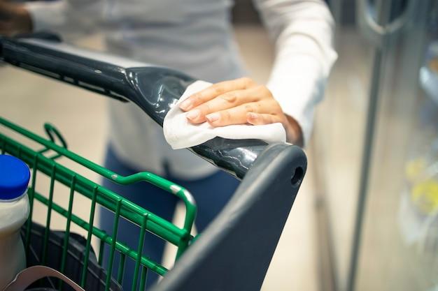 Desinfektion des einkaufswagens der frau mit desinfektionsmittel vor gebrauch wegen koronavirus-pandemie