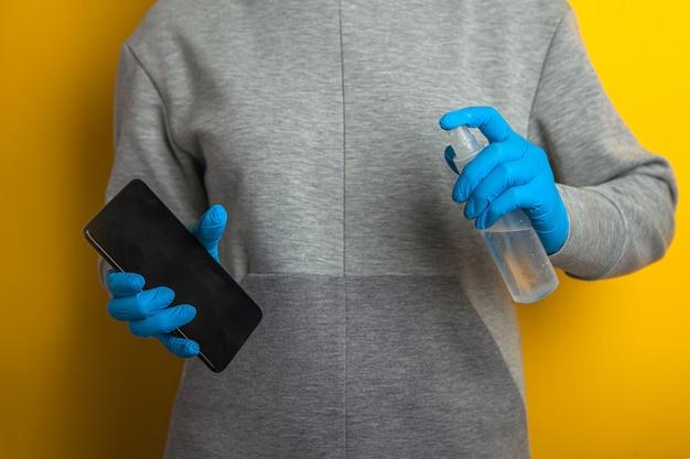 Desinfektion des telefons. eine frau in gummihandschuhen hält ein telefon und einen sprühdesinfektor in den händen.