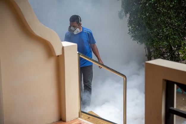 Desinfektion durch viren. ein mann in einem atemschutzgerät sprüht ein antiseptikum.