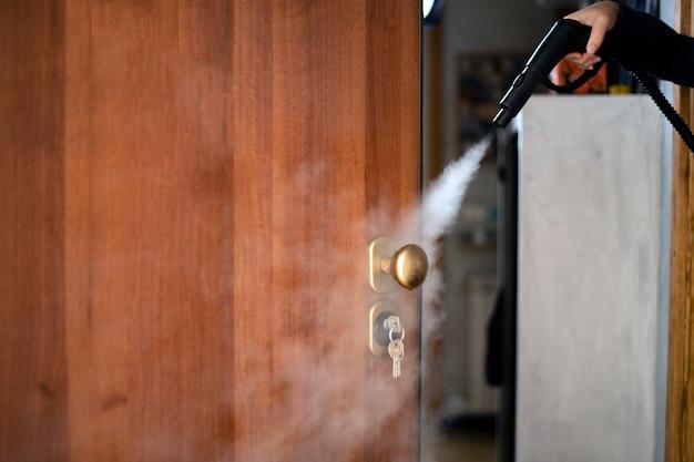 Desinfektion und desinfektion mit dampf zu hause, dampfstrom wird zum türgriff und den schlüsseln im schloss geleitet