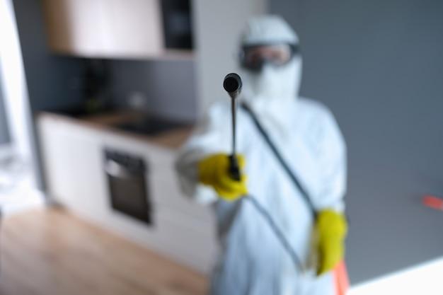 Desinfektionsmittel im schutzanzug, der spray mit flüssigkeit hält, um insekten zu töten, nahaufnahme
