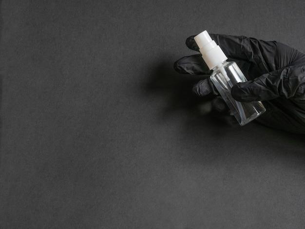 Desinfektionsmittel in einer flasche mit spray zur behandlung von händen und verschiedenen oberflächen während einer epidemie in einer hand in einem schwarzen einweghandschuh