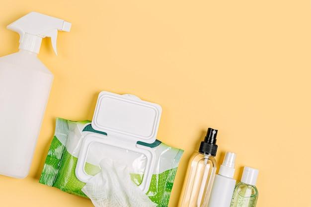 Desinfektionsspray mit antibakteriellen feuchttüchern und handdesinfektionsmittel auf gelbem hintergrund. persönliches hygieneprodukt zum schutz vor viren, grippe, coronavirus, covid-19