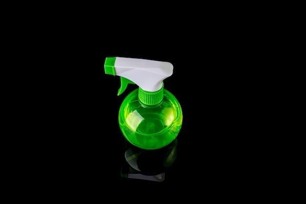 Desinfektionssprühflasche lokalisiert auf schwarzem hintergrund. haushaltsreinigung verhindern