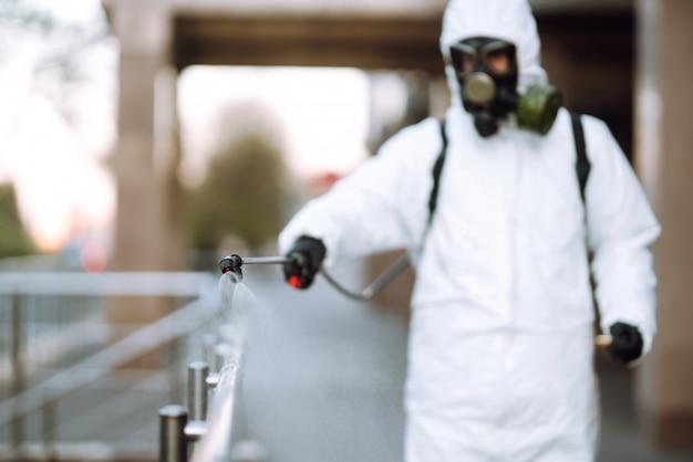 Desinfektionssprühgeräte mit sprühchemikalien auf das geländer an der leeren öffentlichen stelle im morgengrauen in der stadt der quarantäne. covid 19. reinigungskonzept.