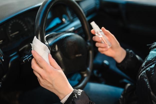 Desinfektionstücher. sprühen von antibakteriellem desinfektionsspray auf lenkradauto, infektionskontrollkonzept. verhindern sie coronavirus, covid-19, grippe. frauenhände, die ein auto fahren.