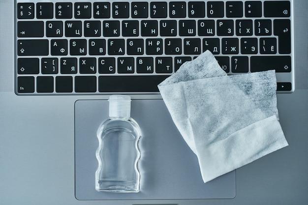 Desinfiziert und reinigt die funktionierende tastatur mit antibakteriellen feuchttüchern und einer antiseptischen gelflasche zum schutz vor coronavirus-ausbruch