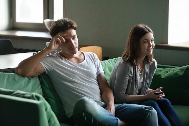 Desinteressierter freund, der während aufgeregte freundin, die fernsehserie aufpasst, gelangweilt wird