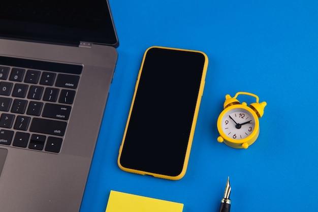 Desktop, arbeitsbereich für die arbeit zu hause. smartphone für text auf blauem hintergrund.