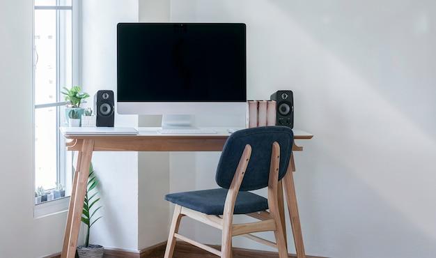 Desktop-computer mit schwarzem bildschirm auf holztisch im modernen raum.