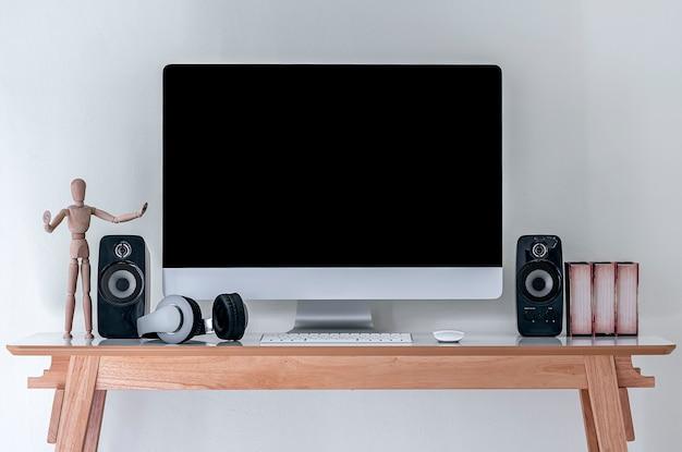Desktop-computer mit schwarzem bildschirm mit lautsprechern und kopfhörer auf holztisch.
