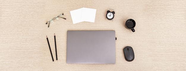 Desktop für online-schulungen, remote-arbeiten und arbeiten von zu hause aus. geschlossener laptop, tasse schwarzen kaffee, gläser, stifte auf tisch.