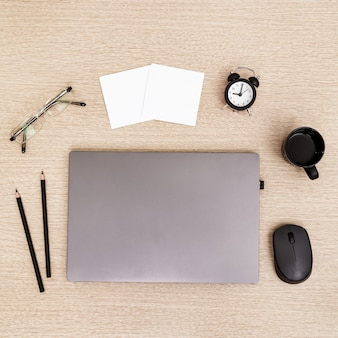 Desktop für studenten oder freiberufler. arbeitsplatz. arbeitsplatz mit grauem modernem laptop, tasse kaffee, gläsern und uhr zur zeitsteuerung auf leuchttisch. flach liegen.