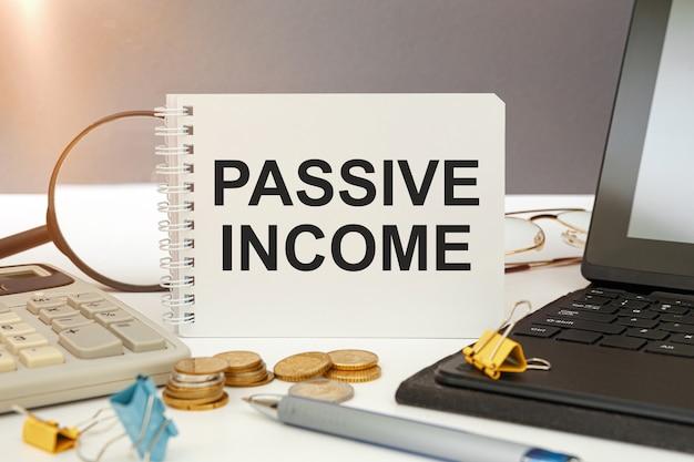 Desktop mit dokumenten, taschenrechner und notizbuch mit der aufschrift passive income