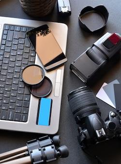 Desktop mit fotoausrüstung, kamera, stativ, blitz und computer