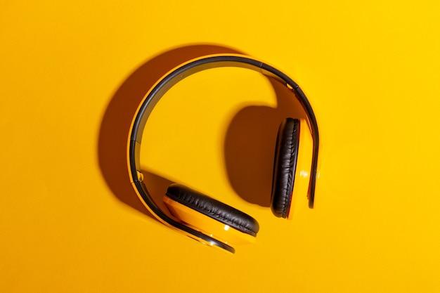 Desktop mit gelben kabellosen kopfhörern auf einem leuchtend gelben hintergrund