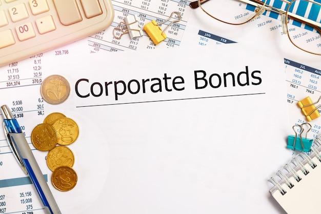Desktop-schreibtisch, notebook, brille, stift und dokumente mit corporate bonds-aufschrift