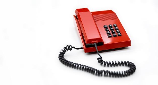 Desktop-telefon aus den 80er jahren und rote farbe auf weißem hintergrund isoliert. platz für text. kommunikationskonzept.
