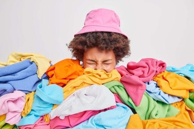 Desorganisierte frau mit lockigen haaren steckt den kopf aus dem kleiderhaufen