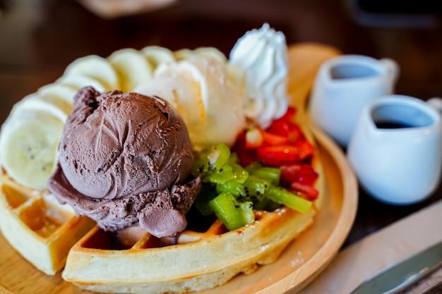 Dessert aus brownie und grüntee-eis zusammen mit schlagsahne auf dem weißen teller