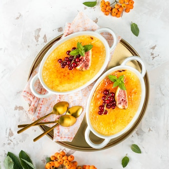 Dessert crème brlée mit frischen feigen und johannisbeeren und minzblättern in weißen schalen auf hellem steinhintergrund in einer herbstkomposition. leckeres dessert für zwei. platz. ansicht von oben