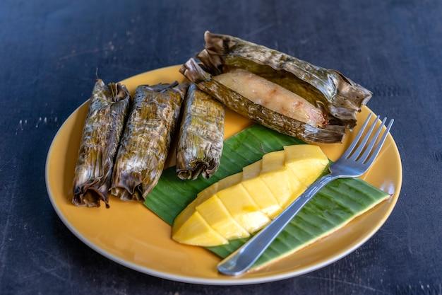 Dessert im thailändischen stil, gelbe mango mit klebrigem bananenreis in palmblättern. gelbe mango und klebriger reis ist ein beliebtes traditionelles dessert von thailand. nahaufnahme