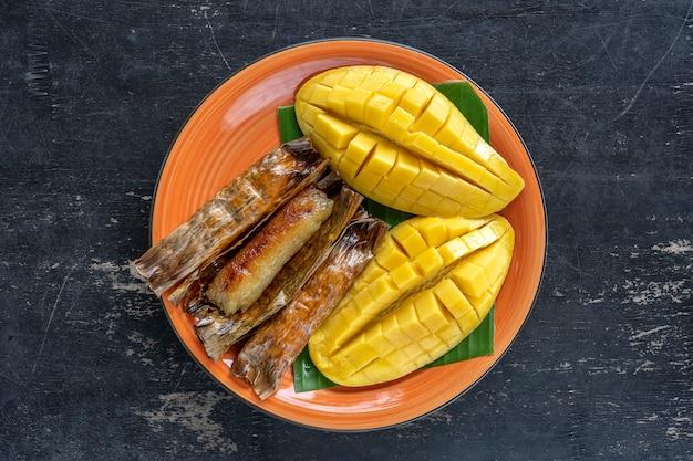 Dessert im thailändischen stil, gelbe mango mit klebrigem bananenreis in palmblättern. gelbe mango und klebriger reis ist ein beliebtes traditionelles essen thailands. nahaufnahme