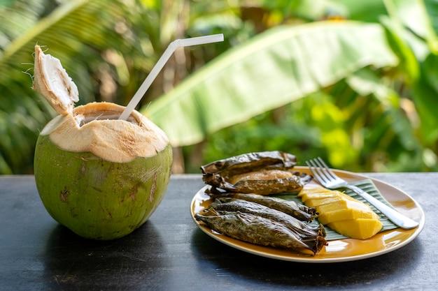 Dessert im thailändischen stil, gelbe mango mit klebrigem bananenreis in palmblättern und grüner kokosnuss. gelbe mango und klebriger reis ist ein beliebtes traditionelles dessert von thailand. nahaufnahme