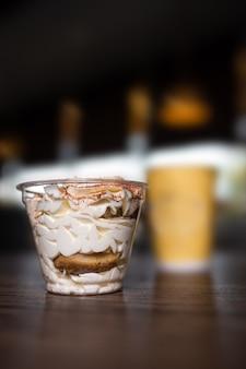 Dessert in einem plastikbecher gegen die oberfläche des kaffees in einem café.