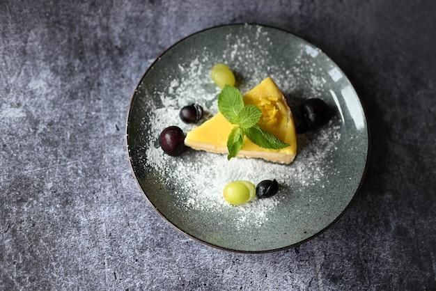 Dessert-käsekuchen auf einem teller mit trauben in einem restaurant mit einem minzblatt