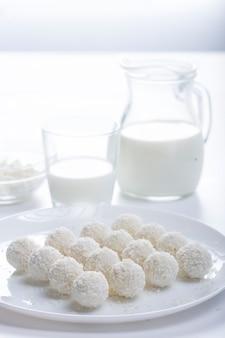 Dessert kokoskuchen und milch im krug auf hellem hintergrund