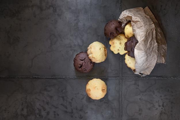 Dessert-, milch- und schokoladenmuffins in einer papiertüte. auf einem grauen betonhintergrund